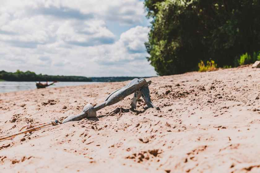gray sand anchor near seashore