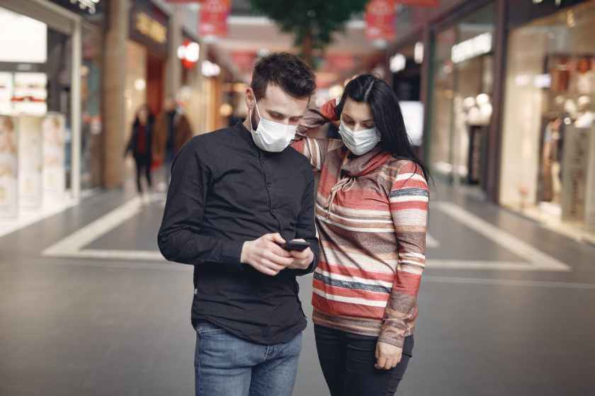 focused young couple wearing medical masks with smartphone in shopping center